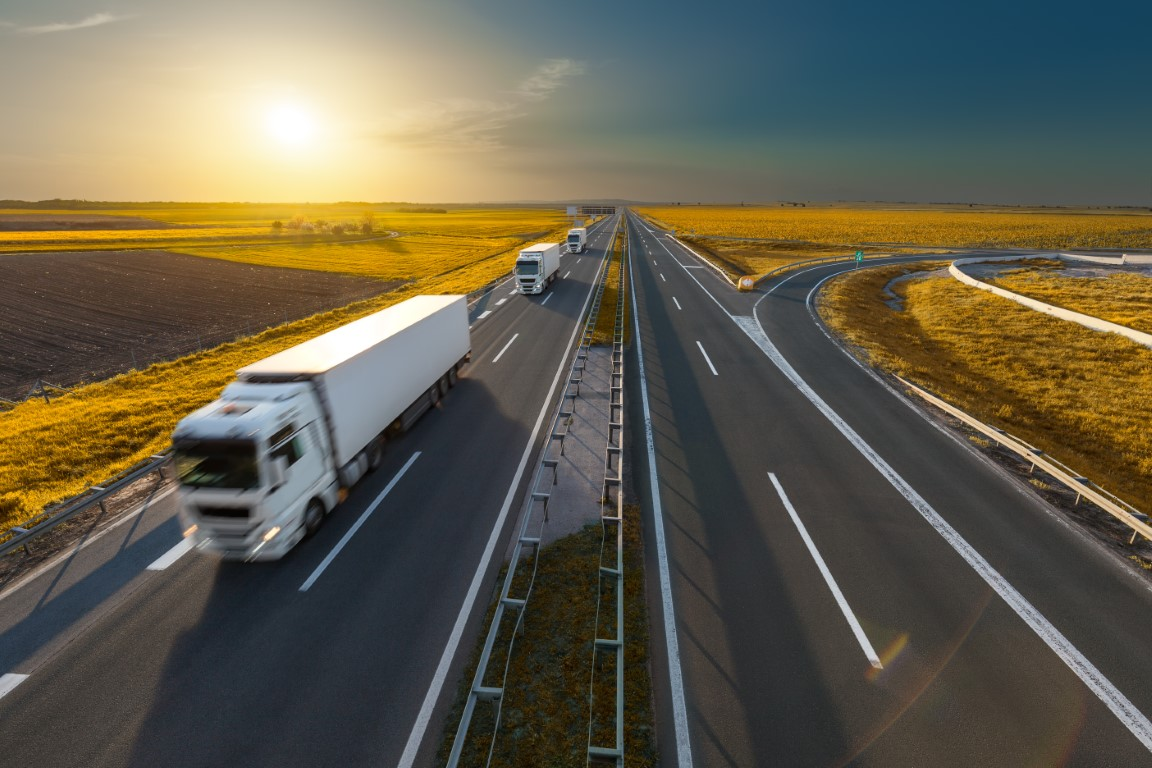 Three trucks on the freeway at idyllic sunset
